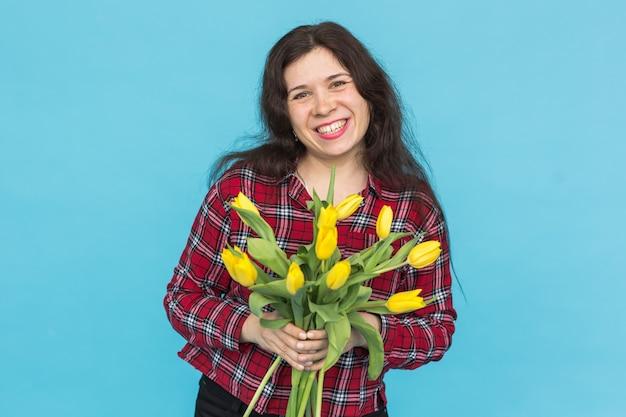 Lachende jonge blanke vrouw met boeket tulpen op blauwe achtergrond.