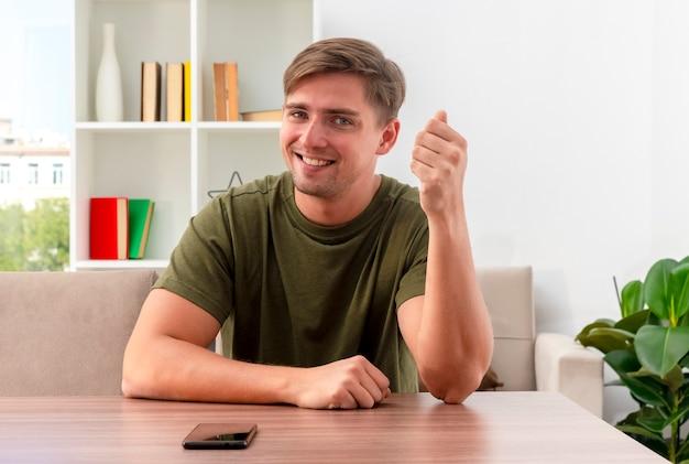 Lachende jonge blonde knappe man zit aan tafel met telefoon vuist houden en kijken naar camera in de woonkamer