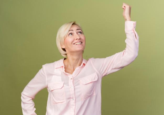 Lachende jonge blonde slavische vrouw die vuist opheft die op olijfgroen wordt geïsoleerd