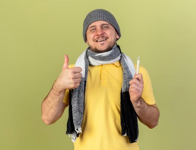 Lachende jonge blonde zieke slavische man met winter hoed en sjaal duimen omhoog