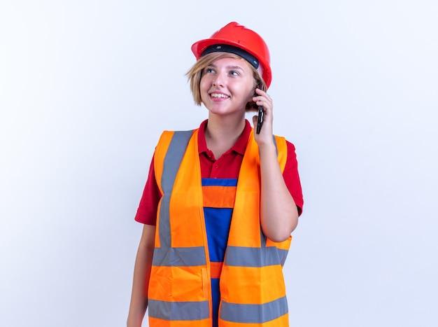 Lachende jonge bouwer vrouw in uniform spreekt op telefoon geïsoleerd op een witte muur