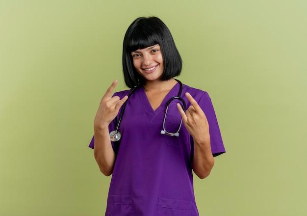 Lachende jonge brunette vrouwelijke arts in uniform met stethoscoop gebaren hoorns handteken met twee handen