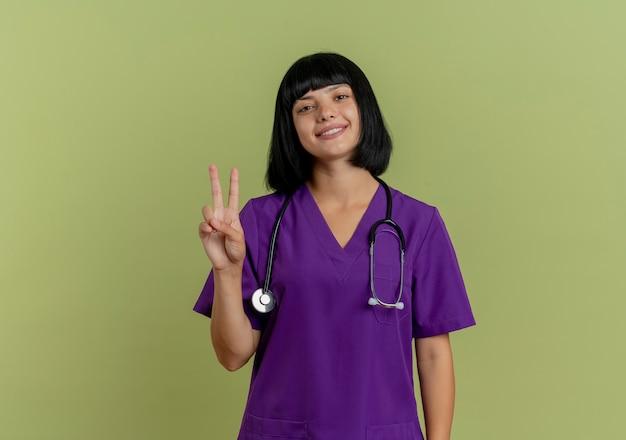 Lachende jonge brunette vrouwelijke arts in uniform met stethoscoop gebaren overwinning handteken geïsoleerd op olijfgroene achtergrond met kopie ruimte