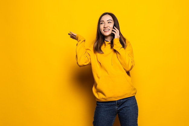 Lachende jonge casual aziatische vrouw praten slimme telefoon geïsoleerd over gele muur