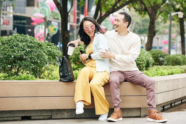 Lachende jonge chinese vrouw die smartphone voor vriendje verbergt wanneer ze op een bankje in het park zitten