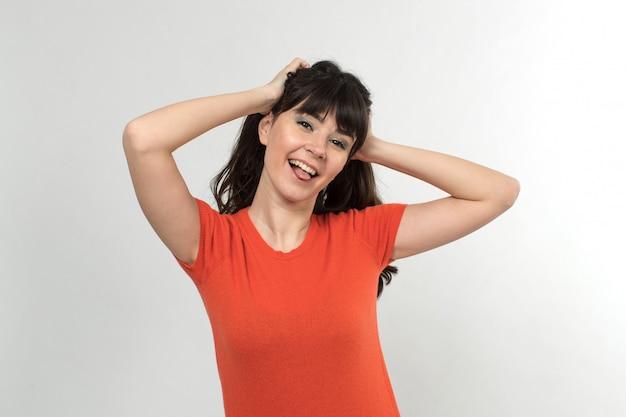 Lachende jonge dame in ontworpen t-shirt in goed humeur met lang haar op wit
