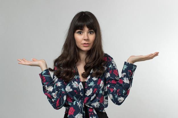 Lachende jonge dame in ontworpen t-shirt opgeheven handen verrast met lang haar op wit