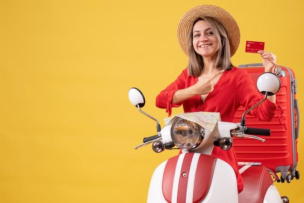 Lachende jonge dame in rode jurk met creditcard in de buurt van bromfiets