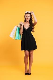 Lachende jonge dame in zwarte jurk met boodschappentassen.