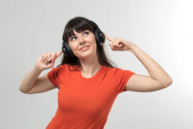 Lachende jonge dame, luisteren naar muziek via oortelefoons in ontworpen t-shirt in goed humeur met lang haar op wit
