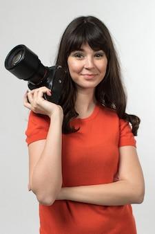 Lachende jonge dame met fotocamera in ontworpen t-shirt in goed humeur met lang haar op wit
