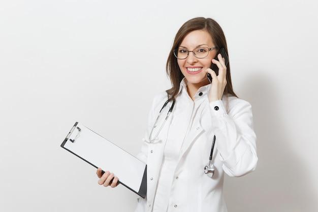 Lachende jonge dokter vrouw met stethoscoop, bril geïsoleerd op een witte achtergrond. vrouwelijke arts in medische toga praat op mobiele telefoon, houd gezondheidskaart op notitieblokmap. gezondheidszorg personeel concept.