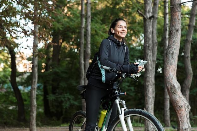 Lachende jonge fitness vrouw rijden op een fiets in het park, luisteren naar muziek met koptelefoon, mobiele telefoon houden