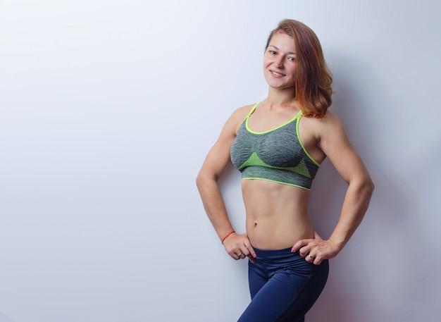 Lachende jonge fitness vrouw spieren in een grijze top zwarte legging geïsoleerd op een witte achtergrond.