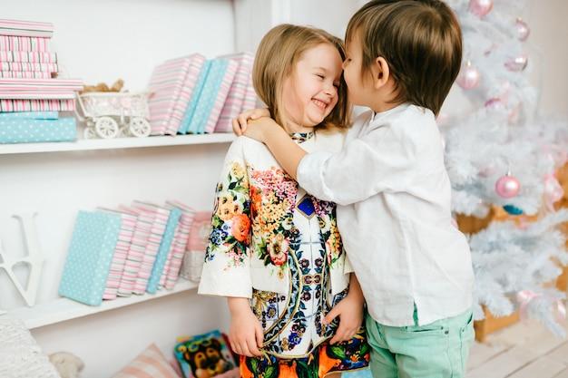 Lachende jonge jongen die zijn mooi meisje in brighruimte koestert met cristmasboom.