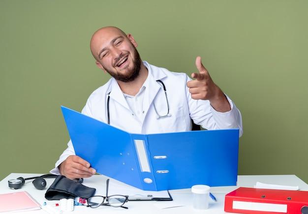 Lachende jonge kale mannelijke arts met een medisch gewaad en een stethoscoop die aan het bureau zit