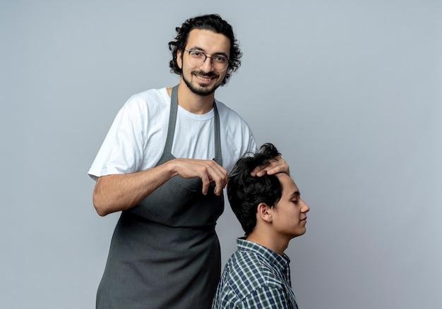 Lachende jonge kaukasische mannelijke kapper bril en golvende haarband dragen uniform doen kapsel voor zijn jonge cliënt geïsoleerd op een witte achtergrond met kopie ruimte