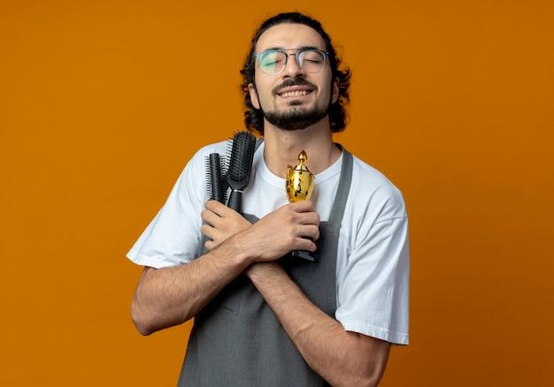 Lachende jonge kaukasische mannelijke kapper bril en golvende haarband dragen uniform houden kammen en winnaar beker met gesloten ogen geïsoleerd op een oranje achtergrond met kopie ruimte
