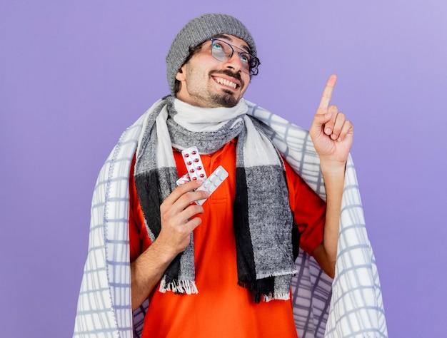 Lachende jonge kaukasische zieke man met bril, muts en sjaal verpakt in geruite bedrijf verpakkingen van medische pillen op zoek en omhoog geïsoleerd op paarse achtergrond