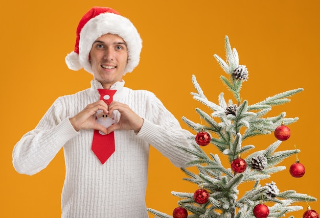 Lachende jonge knappe kerel met kerstmuts en stropdas van de kerstman die in de buurt van een versierde kerstboom staat en een hartteken doet op zoek geïsoleerd op een oranje muur