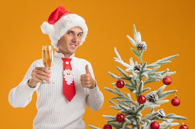 Lachende jonge knappe kerel met kerstmuts en stropdas van de kerstman permanent in de buurt van versierde kerstboom met glas champagne kijken camera weergegeven: duim omhoog geïsoleerd op een oranje achtergrond