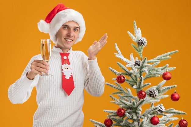Lachende jonge knappe kerel met kerstmuts en stropdas van de kerstman staande in de buurt van versierde kerstboom met glas champagne en kijken met lege hand geïsoleerd op oranje muur