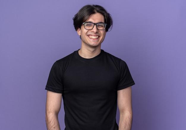 Lachende jonge knappe kerel met zwarte t-shirt en bril geïsoleerd op paarse muur