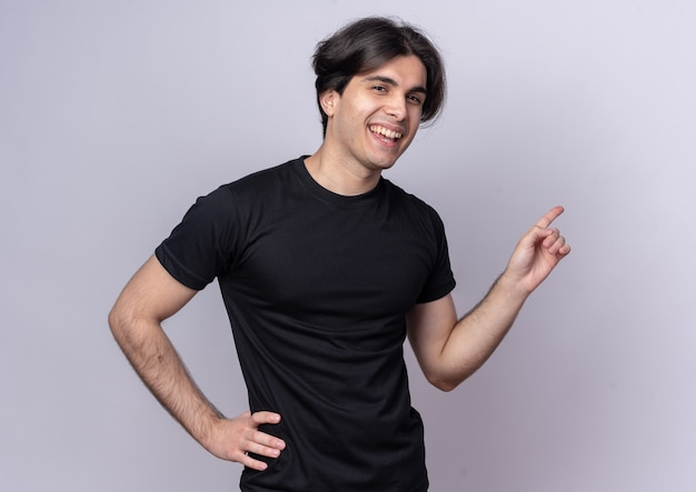 Lachende jonge knappe kerel met zwarte t-shirt wijst naar achteren hand op heup geïsoleerd op een witte muur met kopieerruimte