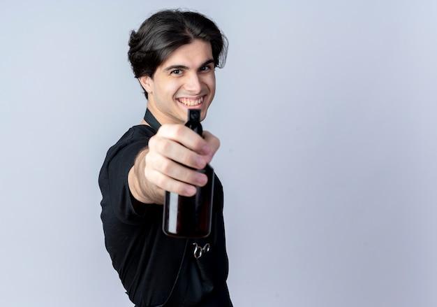 Lachende jonge knappe mannelijke kapper in uniform stak spray fles op camera