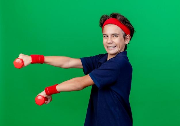Lachende jonge knappe sportieve jongen dragen hoofdband en polsbandjes met beugels staan in profielweergave uitrekkende halters kijken camera geïsoleerd op groene achtergrond met kopie ruimte