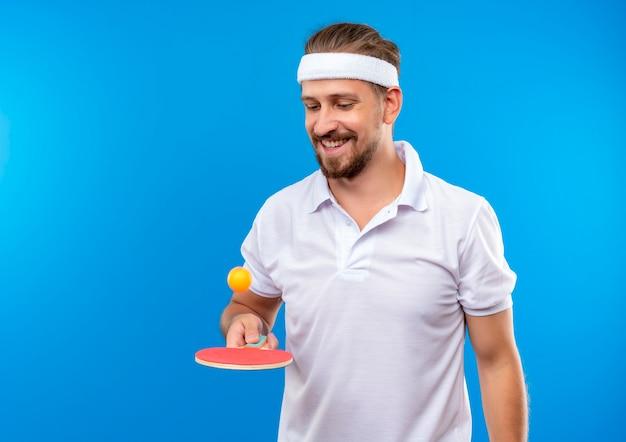 Lachende jonge knappe sportieve man met hoofdband en polsbandjes bal gooien met pingpongracket en kijken ernaar geïsoleerd op blauwe ruimte