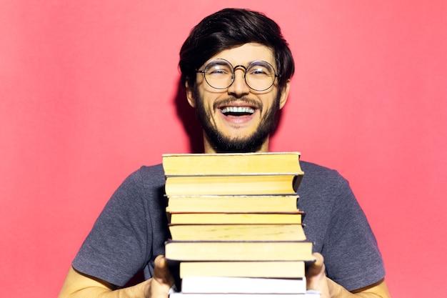 Lachende jonge man, die een stapel boeken vasthoudt, een ronde bril draagt op de muur van koraalroze kleur.