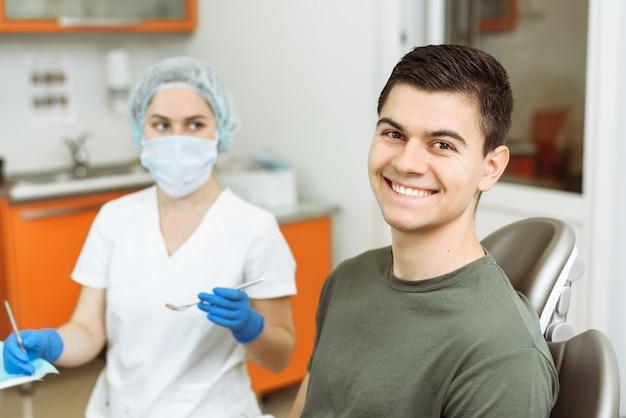 Lachende jonge man in de stoel van een tand met de dokter op de achtergrond