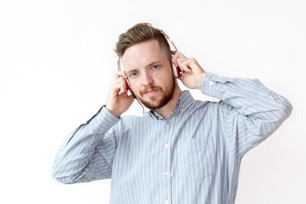 Lachende jonge man luisteren naar muziek in de koptelefoon