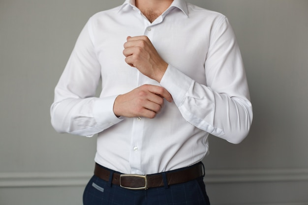 Lachende jonge man maakt de knoppen op het witte shirt binnen vast