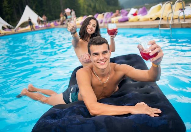 Lachende jonge man met cocktails liggend op een opblaasbare matras in het zwembad