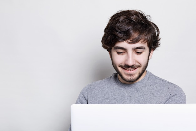 Lachende jonge man met trendy baard en kapsel video-oproep