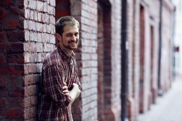 Lachende jonge man tegen de bakstenen muur