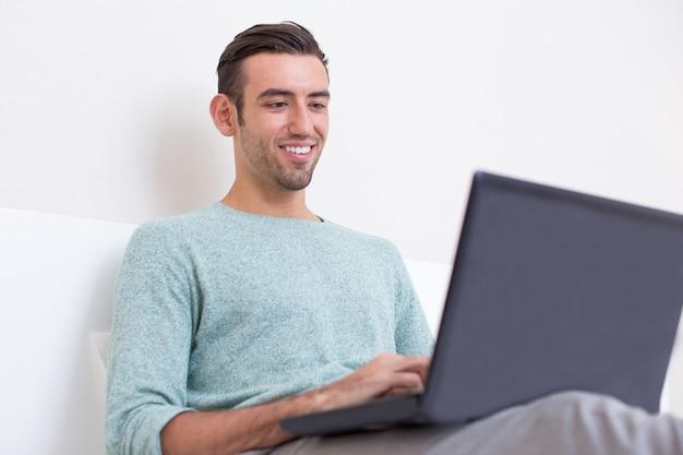 Lachende jonge man werken op laptop op de bank
