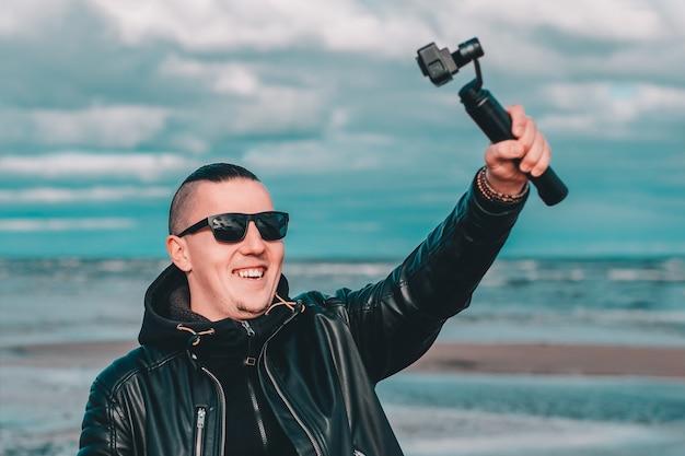 Lachende jonge mannelijke blogger in zonnebril selfie of streaming video maken op het strand met behulp van actiecamera met gimbal camera stabilizer.