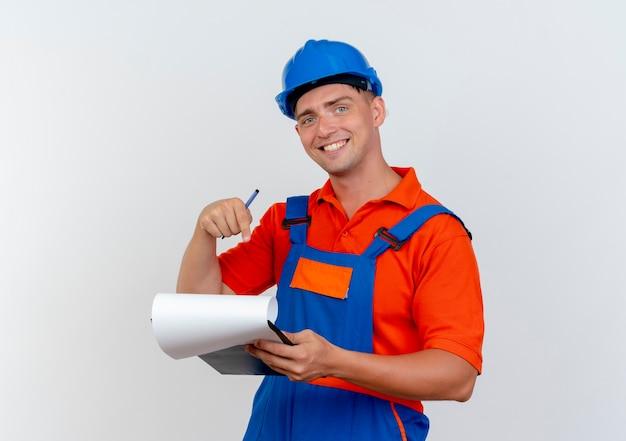 Lachende jonge mannelijke bouwer dragen uniform en veiligheidshelm bedrijf en wijst op klembord