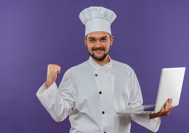 Lachende jonge mannelijke kok in chef-kok uniforme bedrijf laptop en balde vuist geïsoleerd op paarse ruimte