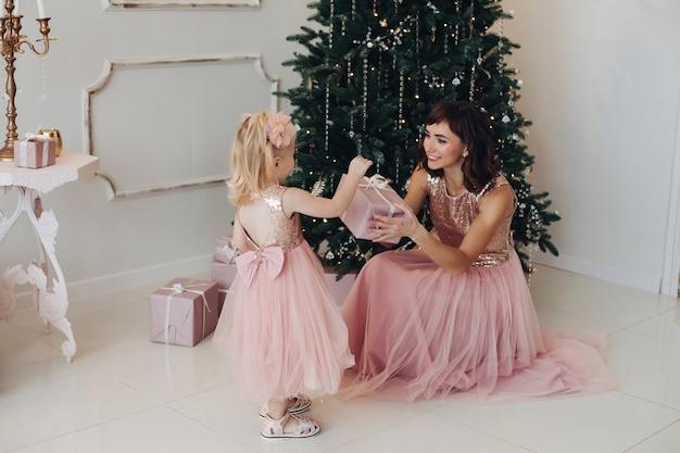 Lachende jonge moeder in geweldige roze avondjurk geschenkdoos te geven aan schattige dochter bij kerstboom achtergrond. gelukkige familie die van het vieren van nieuwjaar geniet bij het volledige schot van de kerstmisdecoratie binnen