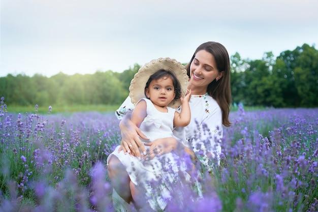 Lachende jonge moeder poseren met kind in lavendelveld