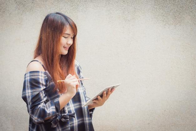 Lachende jonge mooie aziatische vrouw denken met schrijven boek op betonnen muur achtergrond. vintage effect stijl foto's.