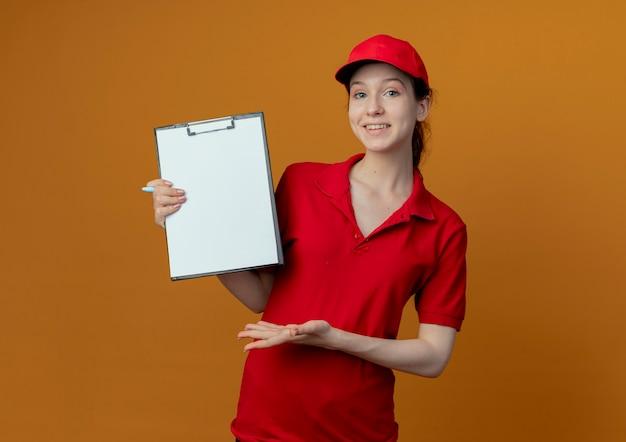Lachende jonge mooie levering meisje in rood uniform en glb bedrijf pen en klembord tonen en met de hand wijzend op klembord geïsoleerd op een oranje achtergrond met kopie ruimte