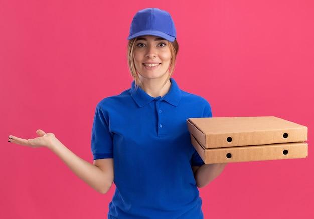Lachende jonge mooie levering meisje in uniform houdt de hand open en houdt pizzadozen op roze
