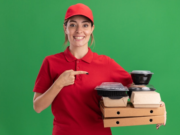 Lachende jonge mooie levering meisje in uniform houdt en wijst op papier voedselpakketten en containers op pizzadozen op groen