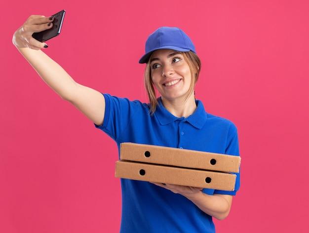 Lachende jonge mooie levering meisje in uniform houdt pizzadozen en kijkt naar de telefoon op roze