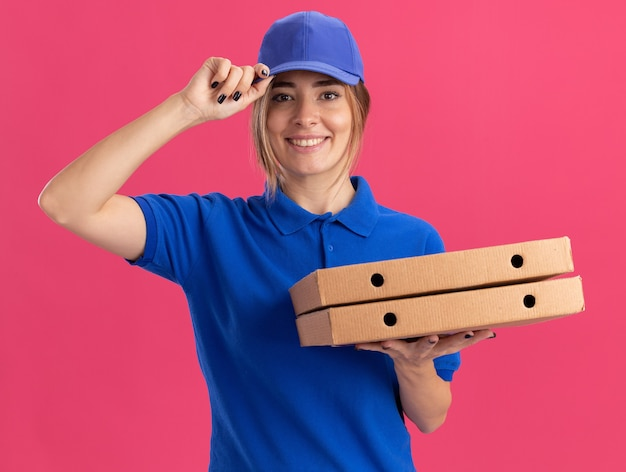 Lachende jonge mooie levering meisje in uniform legt de hand op de dop en houdt pizzadozen op roze